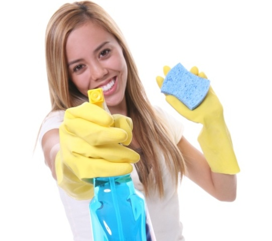 A pretty woman cleaning with spray and sponge