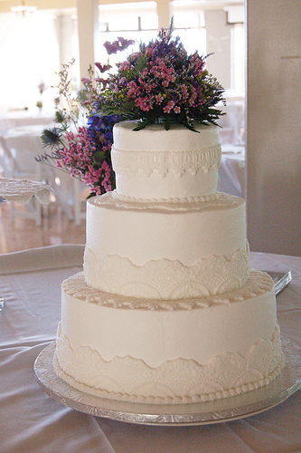 A wedding cake with lace accents and flowers on top.