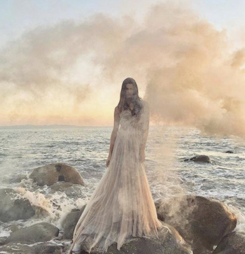 Beautiful bride surrounded in fog standing on rocks in front of the ocean.